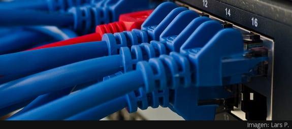 Cableado de red: Varios cables azules y uno rojo conectados a un router
